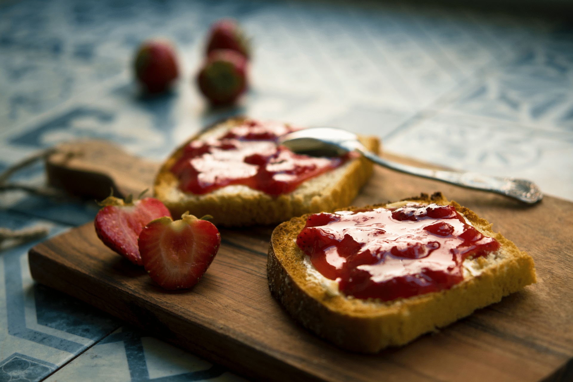toast with strawberry jam on a cutting board