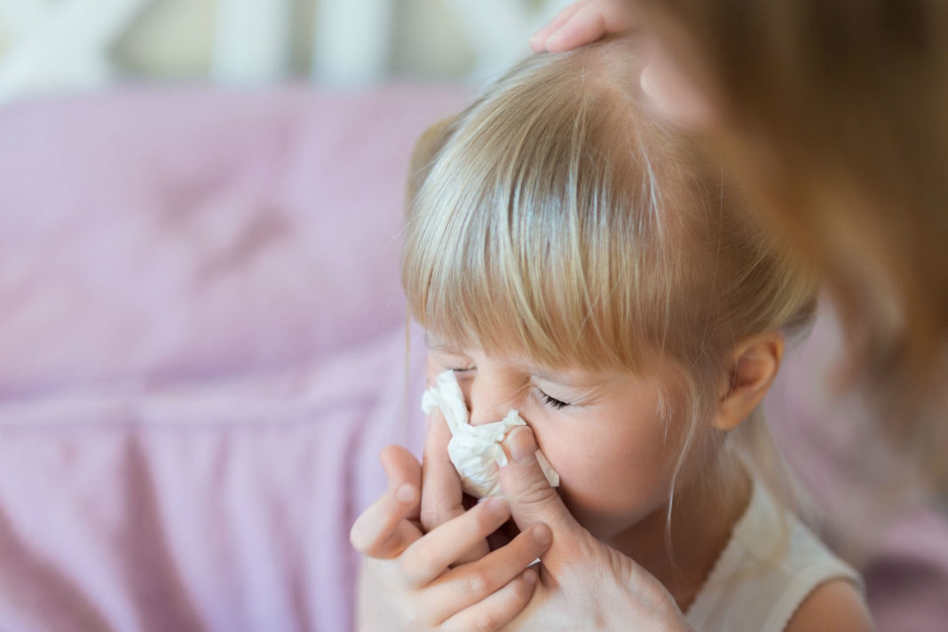 little girl with tissue to her nose