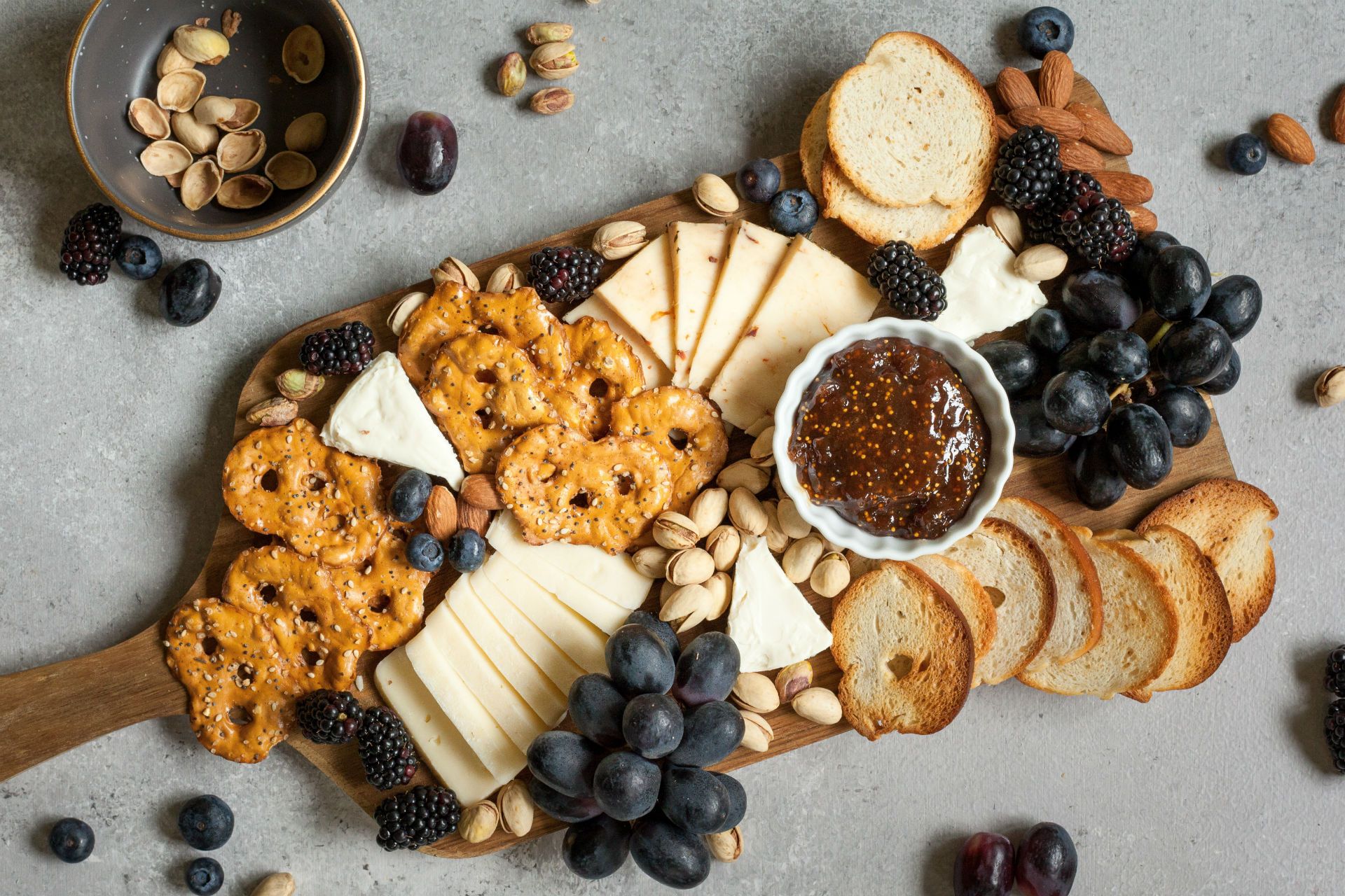 cheeseboard with crackers, fruit and grainy mustard