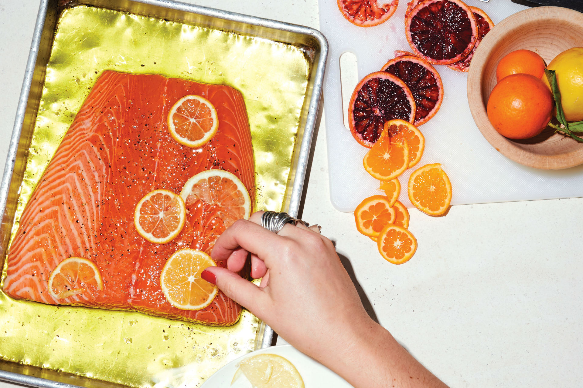 salmon on a sheet pan with citrus slices over it