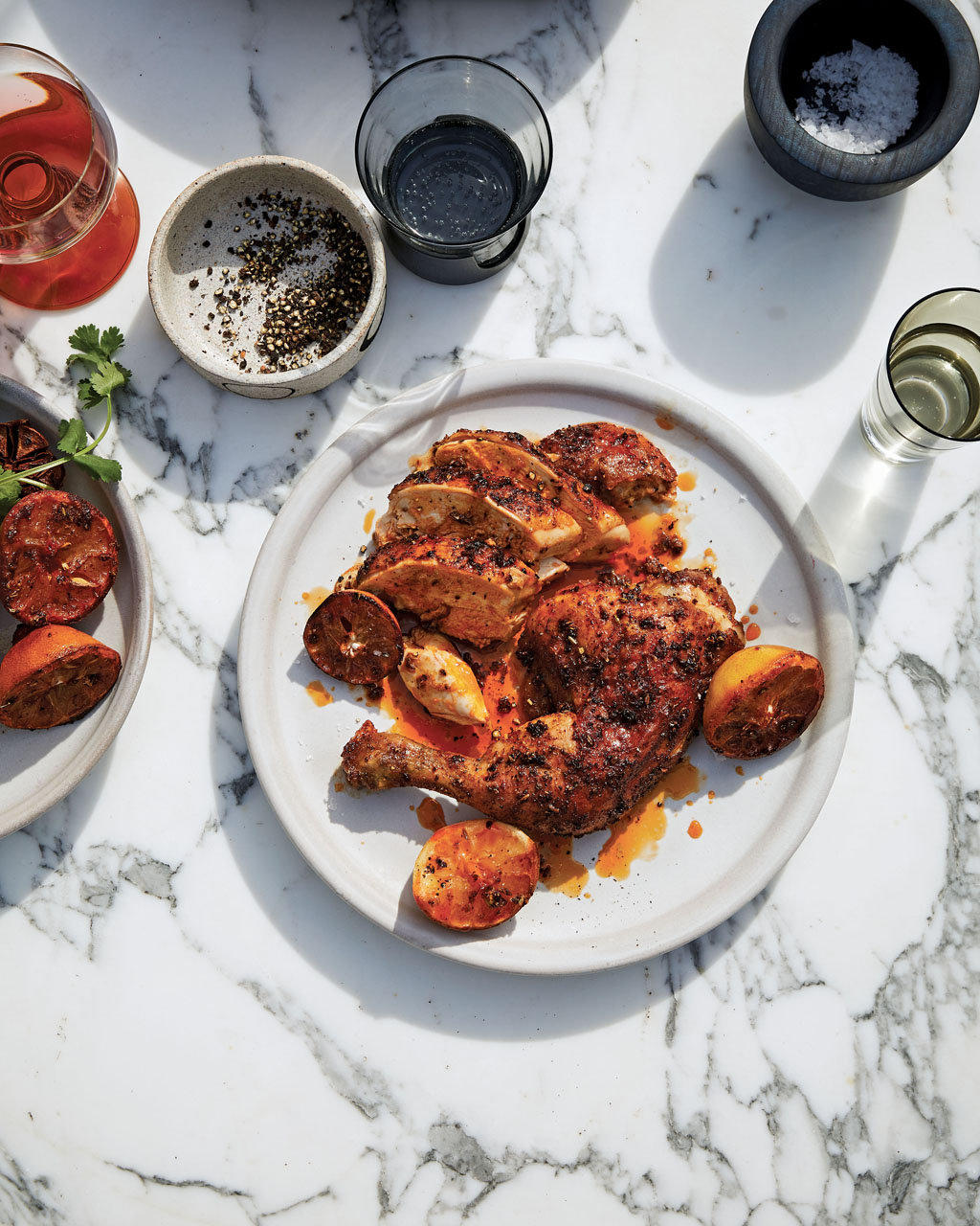 chicken covered in spice with wedges of lemon