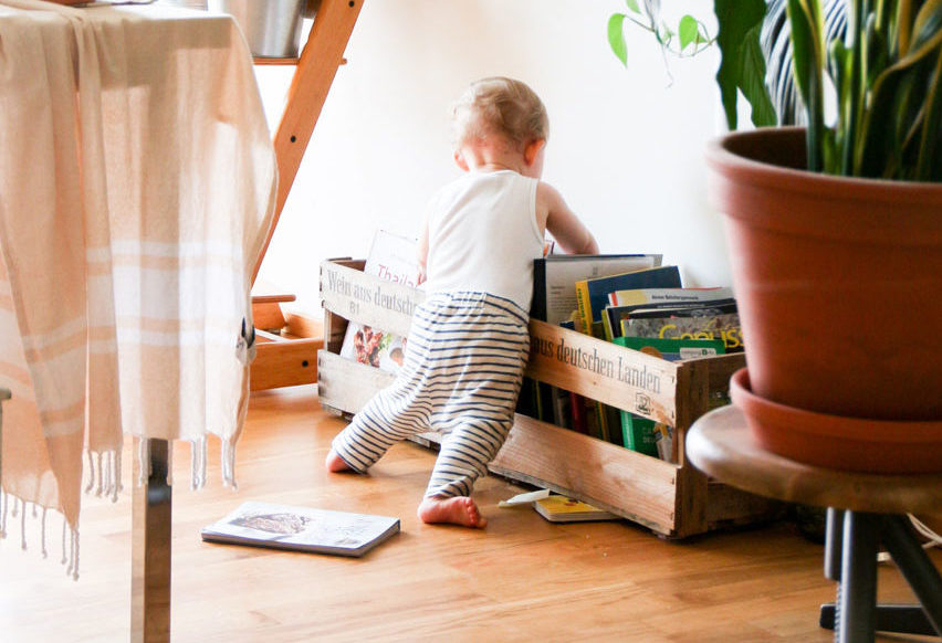 toddler standing at a crate of books