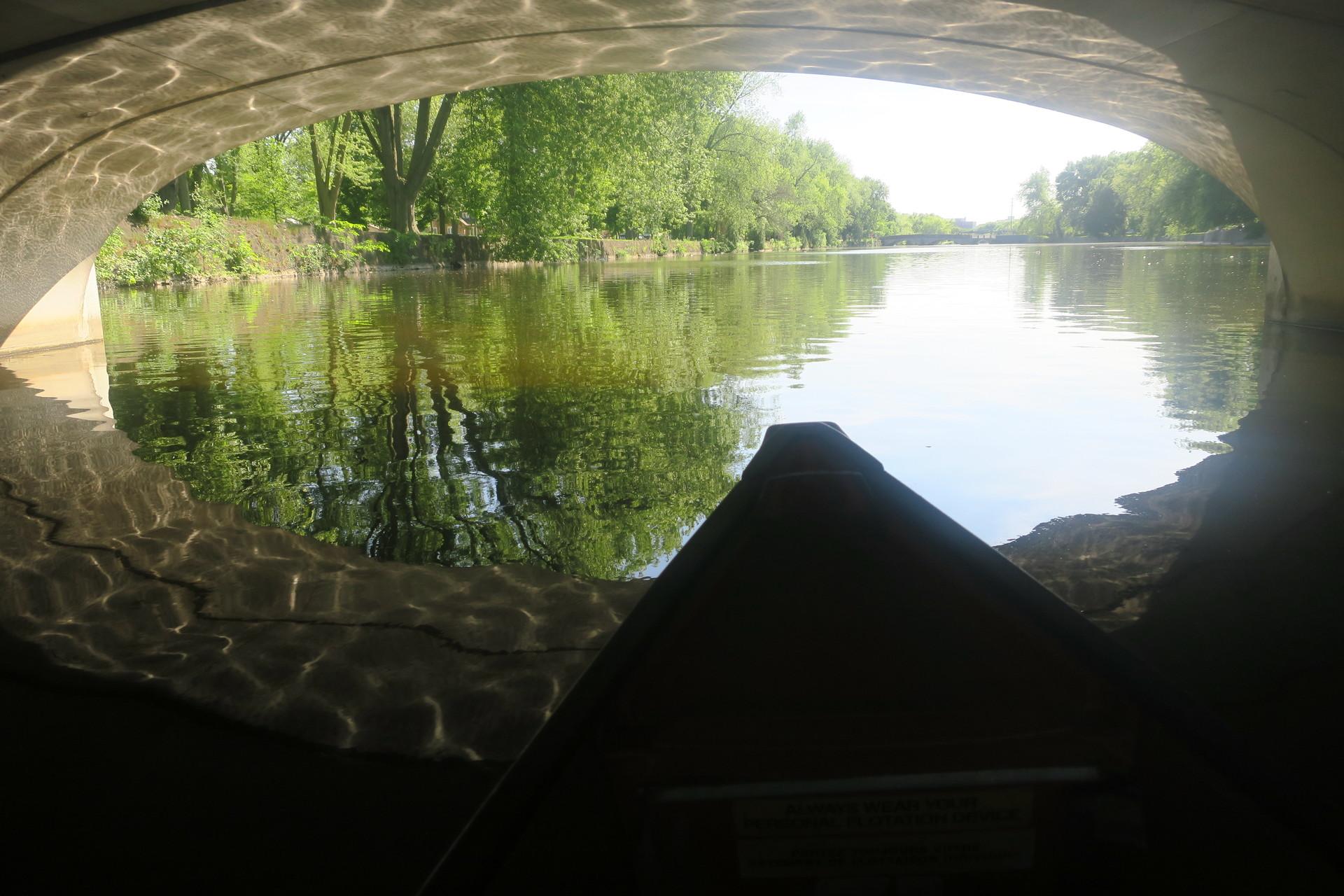 canoeing under a bridge on still water