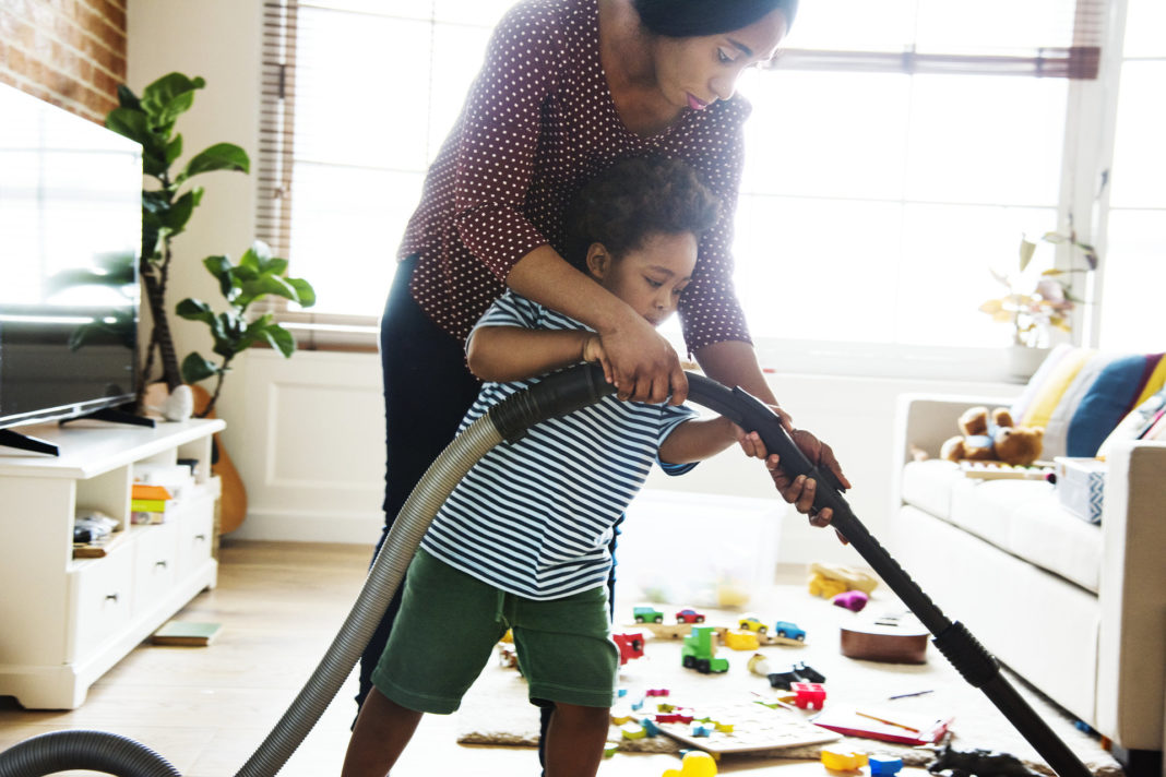 mom helping her son vaccum
