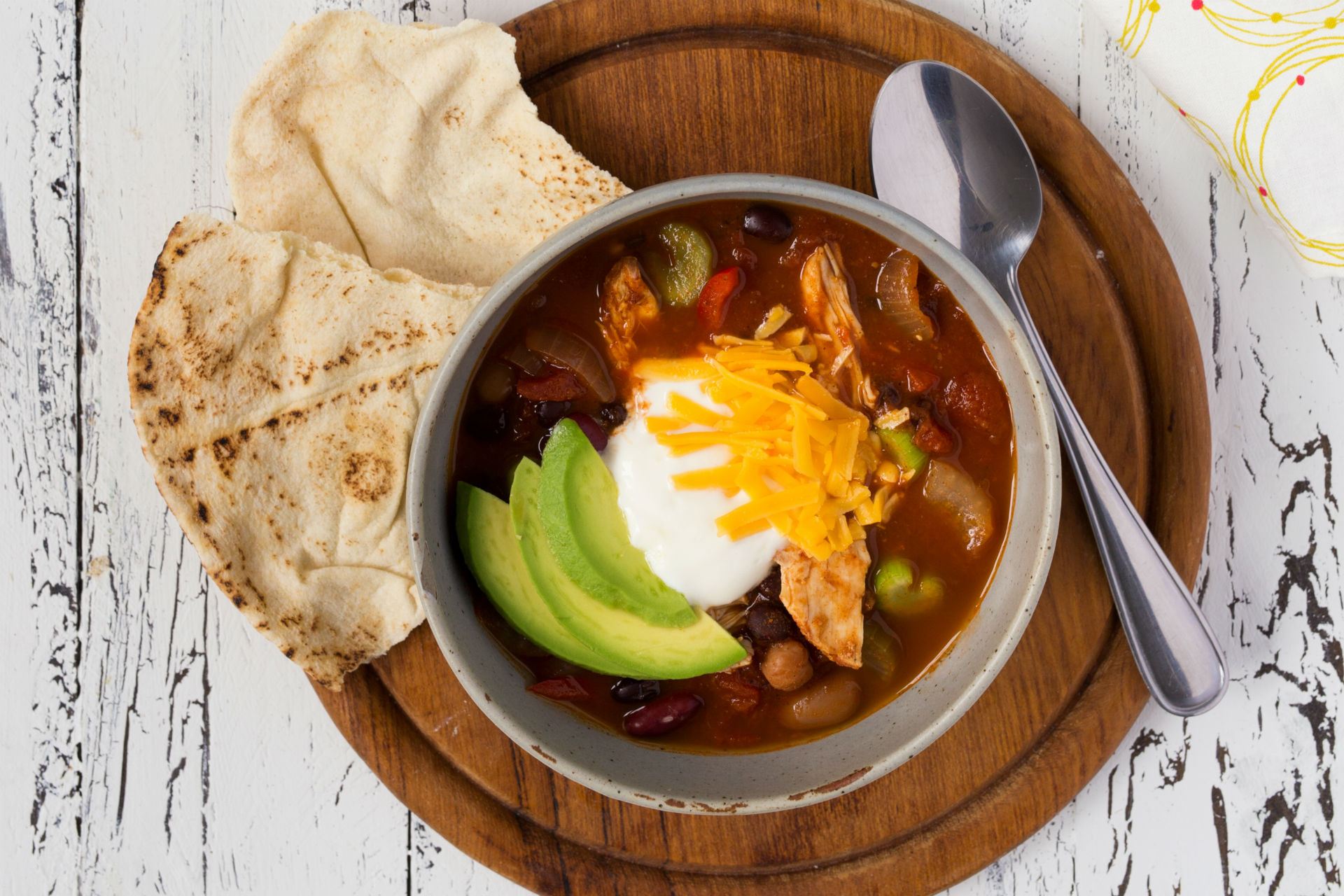 bowl of chili with sour cream, cheese and avocado
