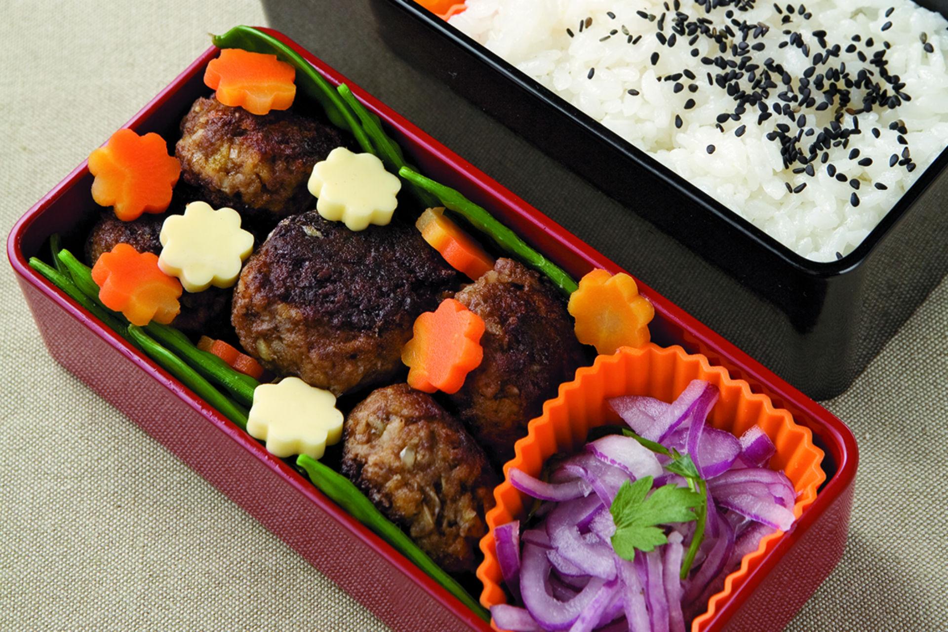 Bento box with mini hamburgers, veggies and rice