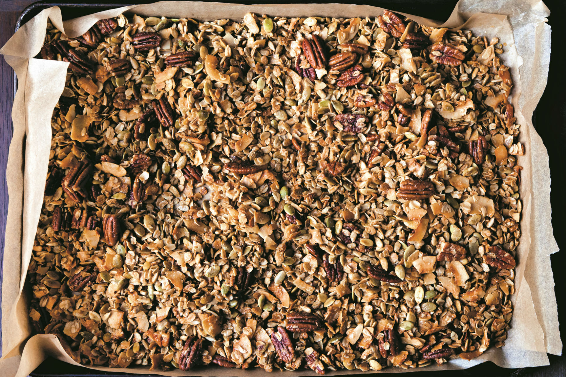 baking sheet of granola with nuts, seeds and coconut