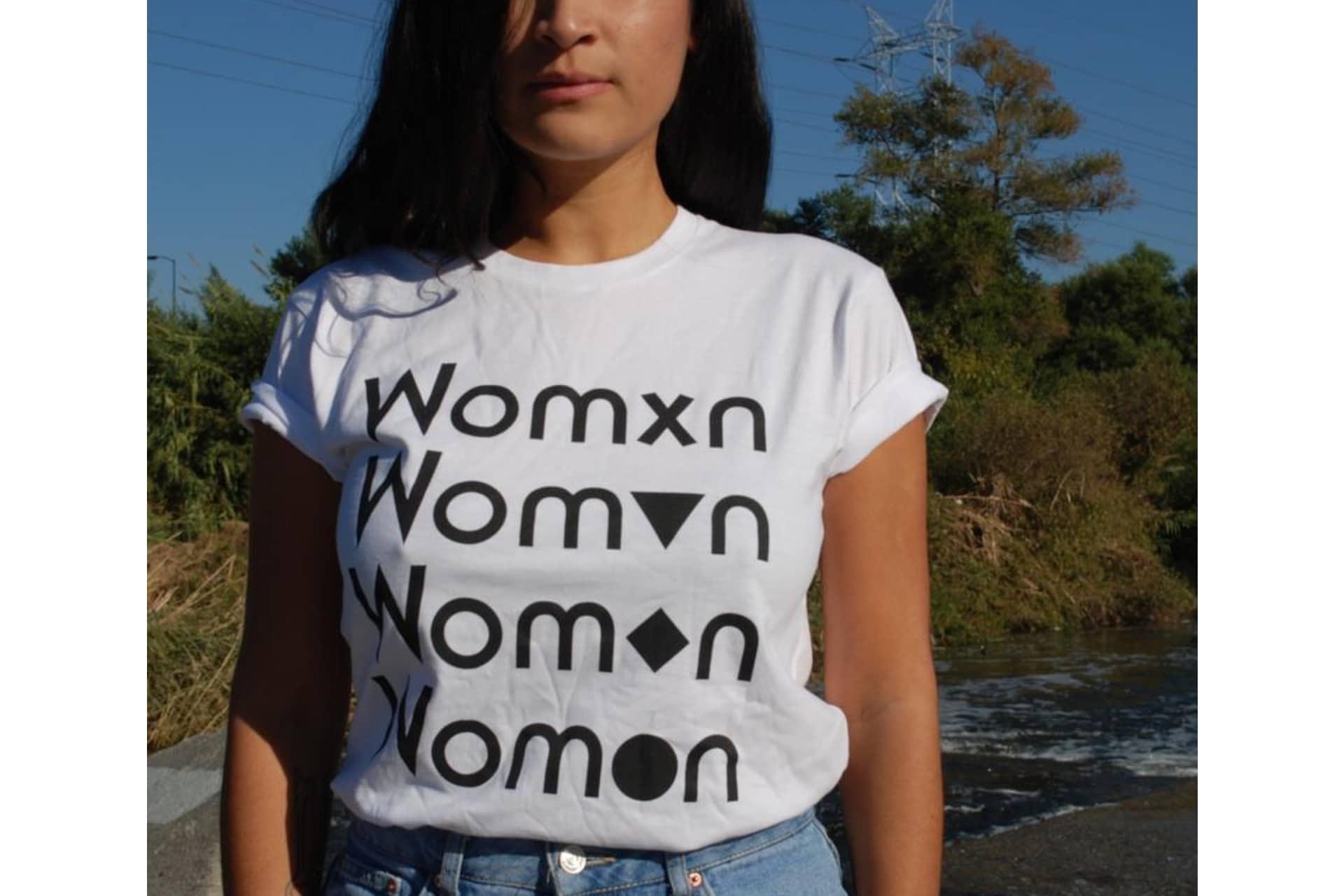 women wearing a whit tshirt that says womxn