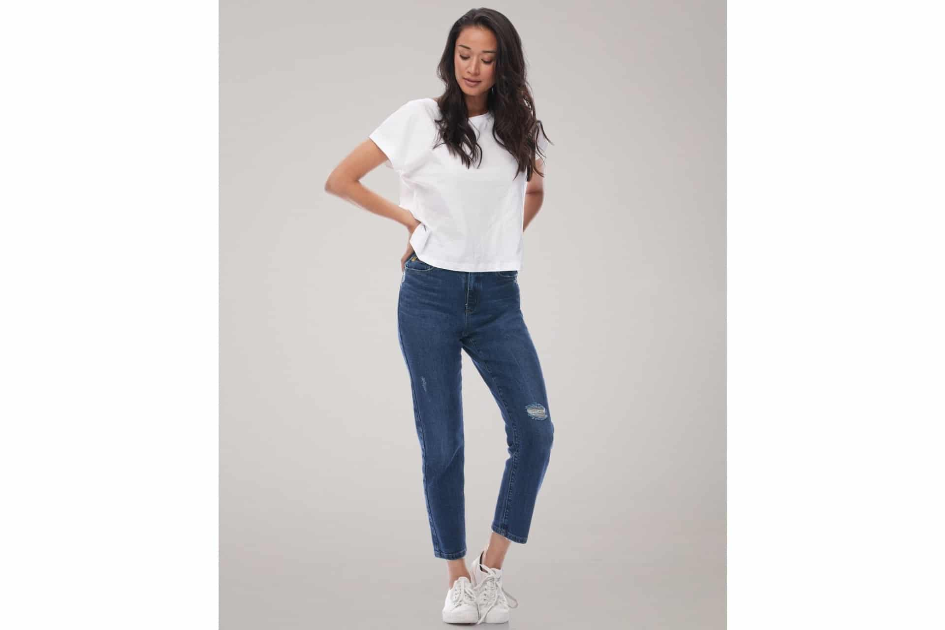 Woman in jeans and a white tshirt looks away from the camera
