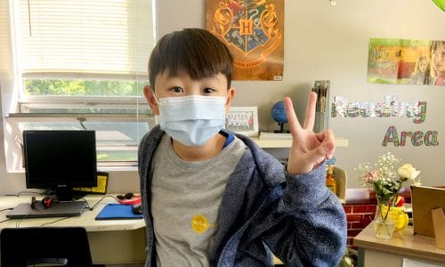 boy wearing mask at school and giving the peace sign