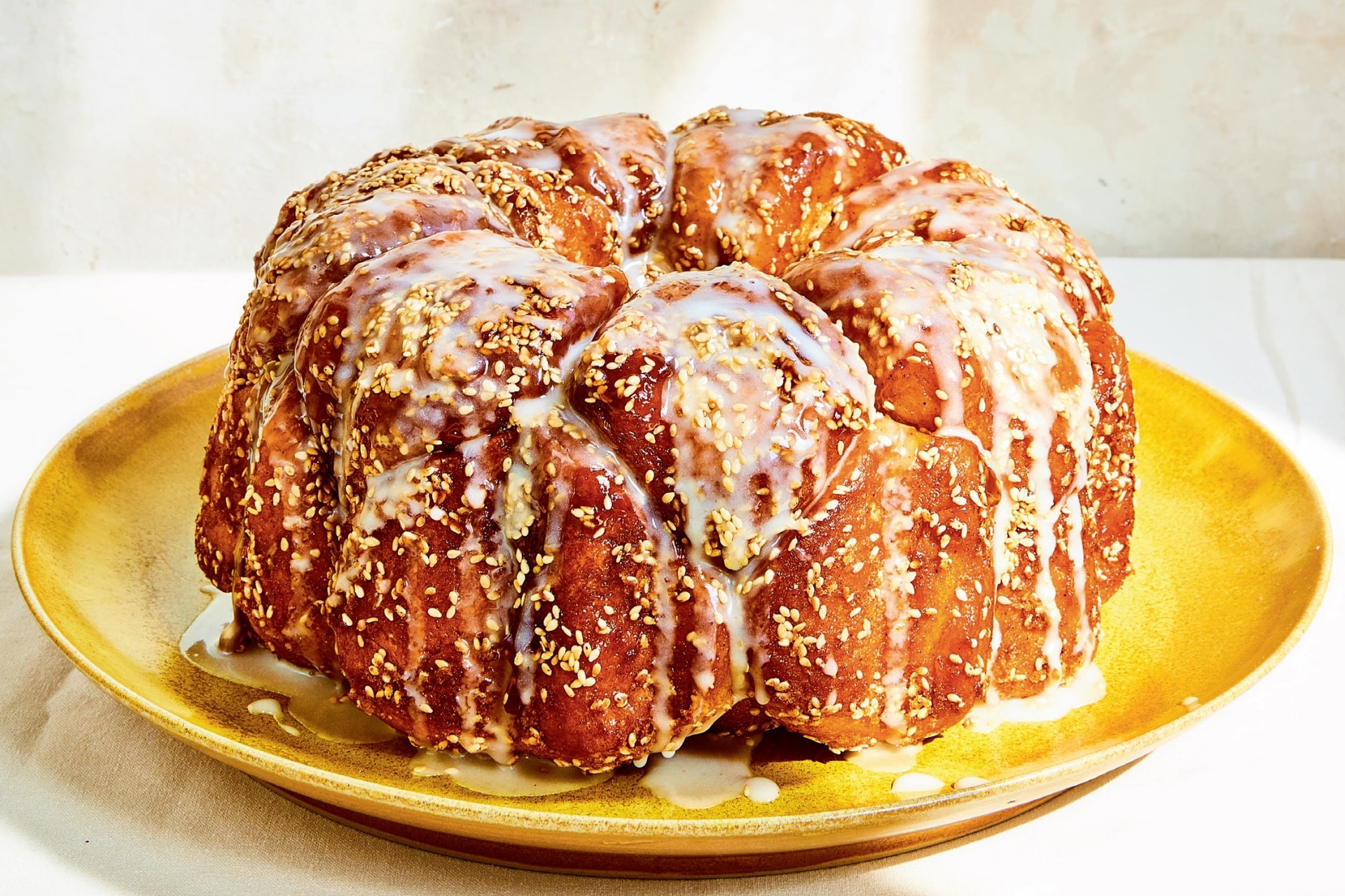 challah monkey bread on a plate with glaze dripping down