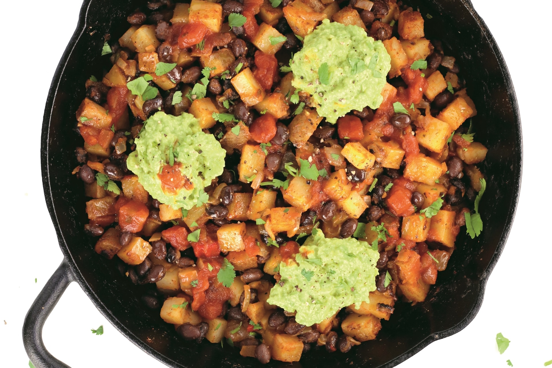 skillet with potato and black bean hash and scoops of guacamole