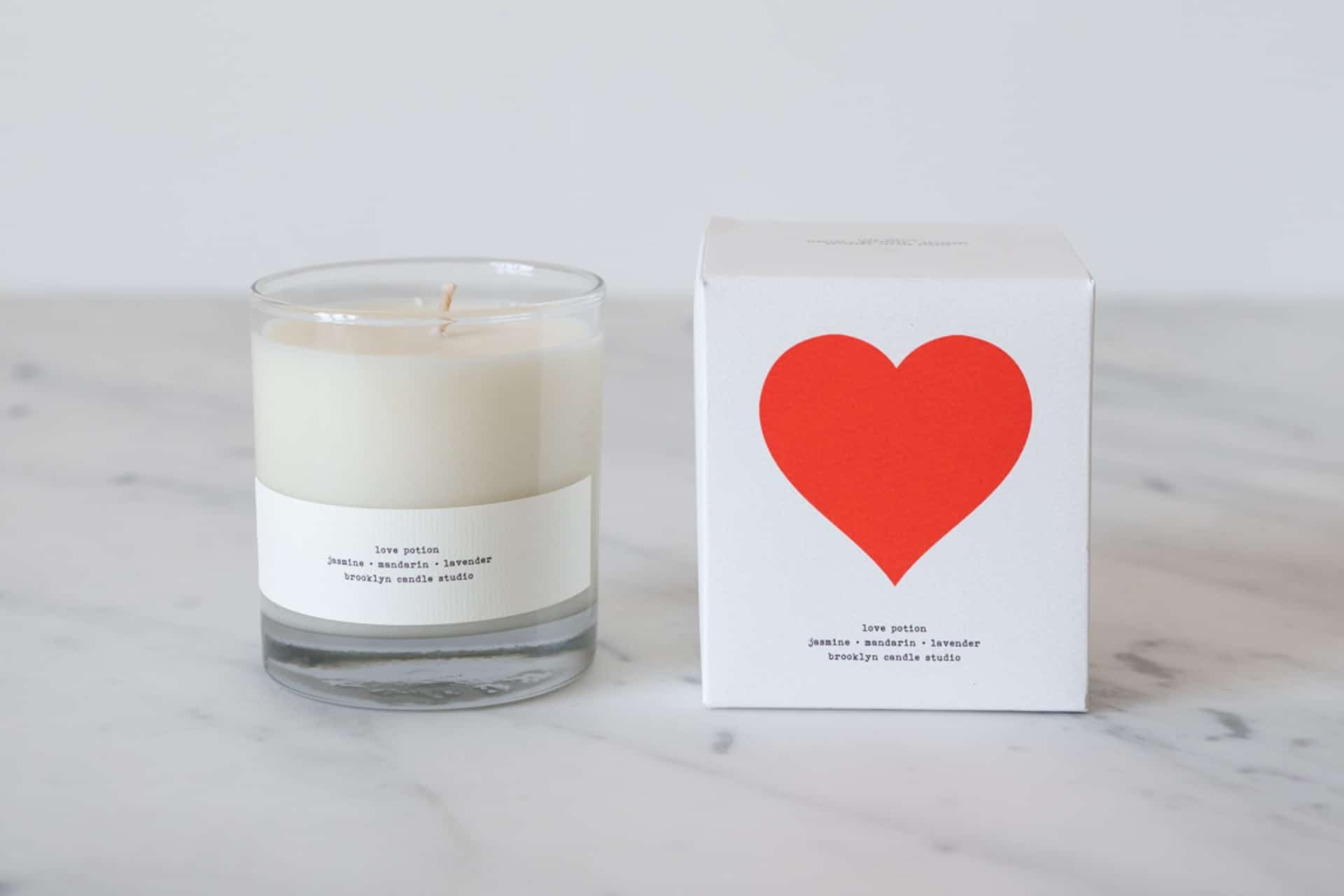 a candle sitting next to a box with a heart on it