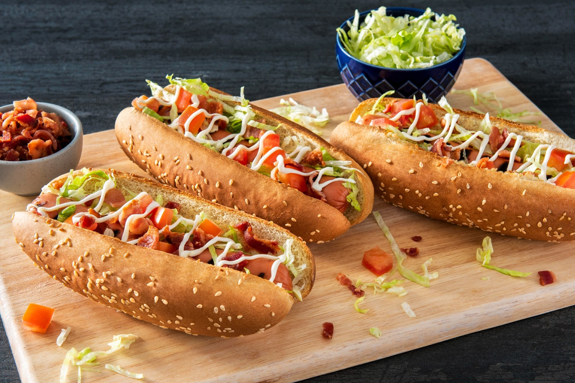 board with hot dogs topped with shredded lettuce, tomatoes and bacon